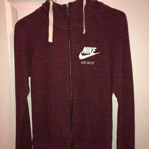 A slim pink Nike jacket with logo on the front.